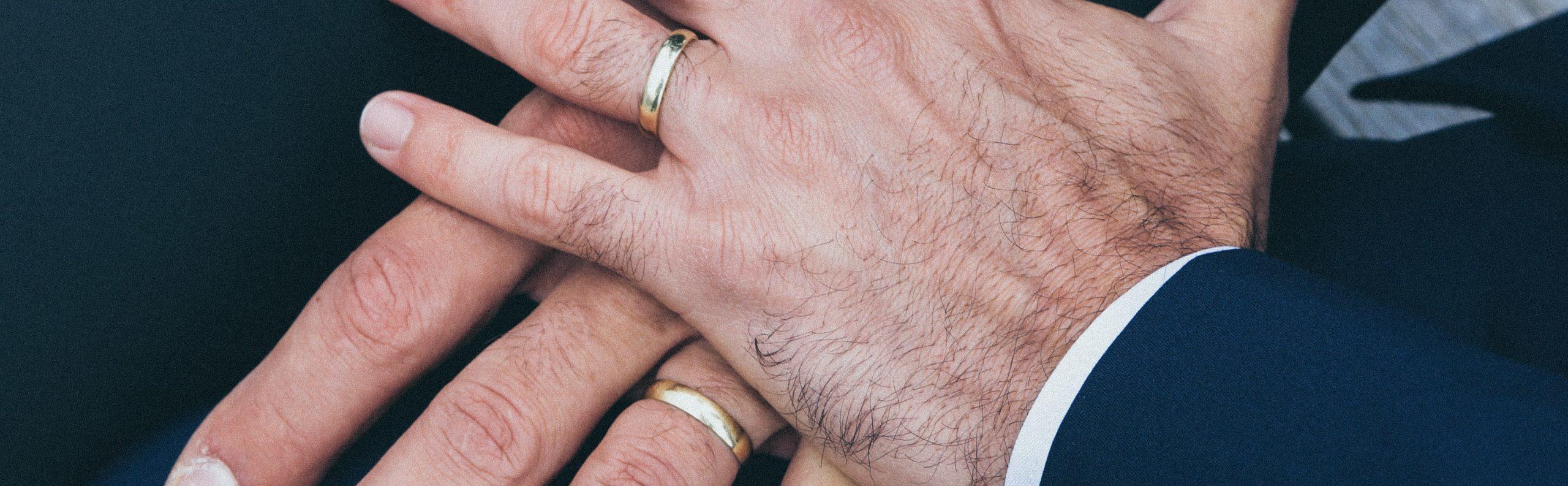 two men showing wedding rings